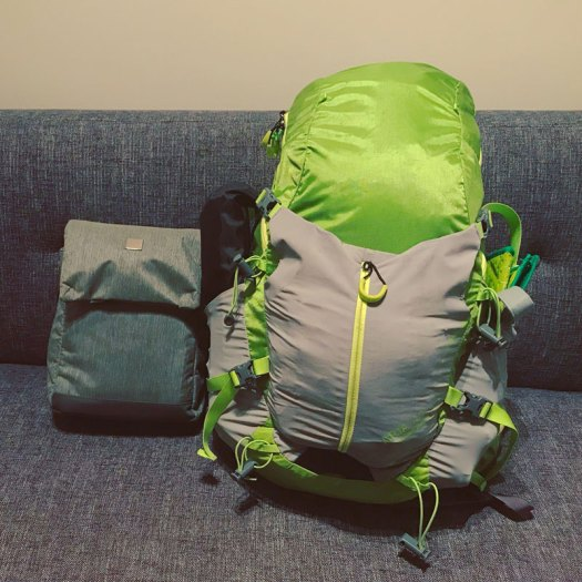 Photo of a packed green backpack and a grey shoulder bag sitting on a couch