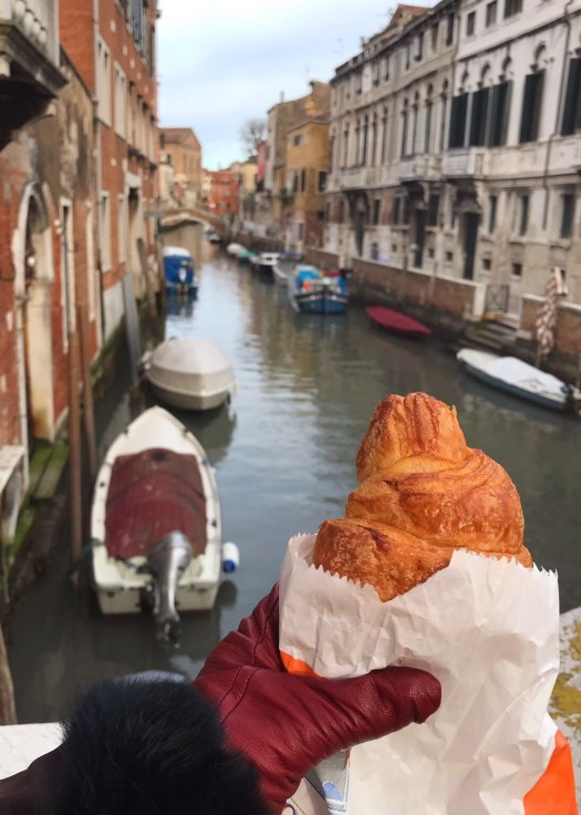 Photo of a croissant being held up next to a canal