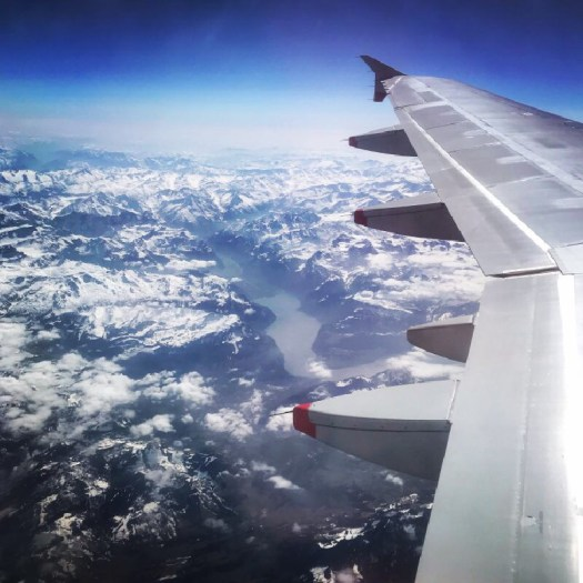 Photo of a plane wing and the Alps from a plane window