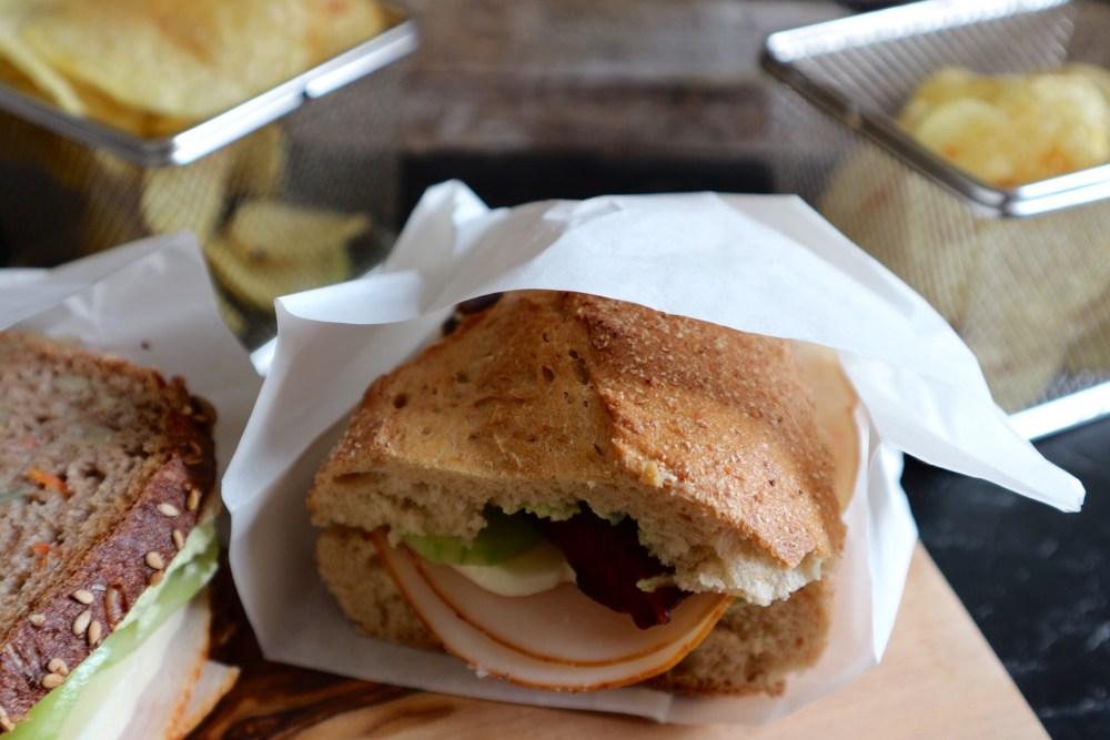 Vollkornbrot, Baguette, gefüllt mit Avocado-Frischkäse, Hähnchen, Mozzarella, Gurke und Speck