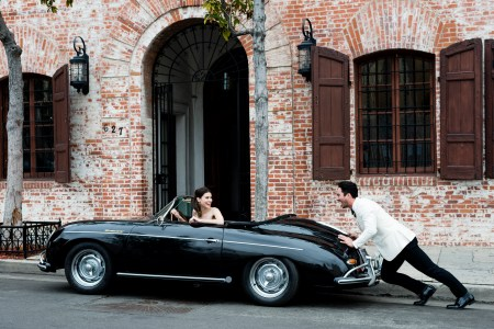 Groom pushes stalled car with bride in it.
