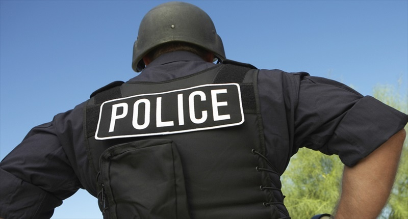 Rear-view-of-policeman-in-uniform-standing-against-car-Shutterstock-800x430