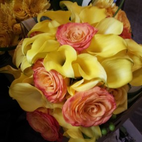 Yellow calla lillies with a pop of circus roses for the bride's bouquet