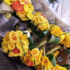 Yellow daisies, circus roses, yellow poms, and bear grass loops for the bridal bouquets