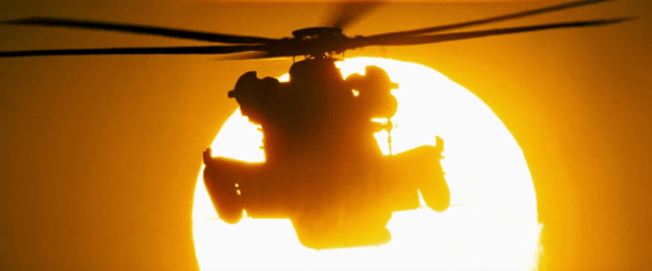 Helicopter flying by the sun