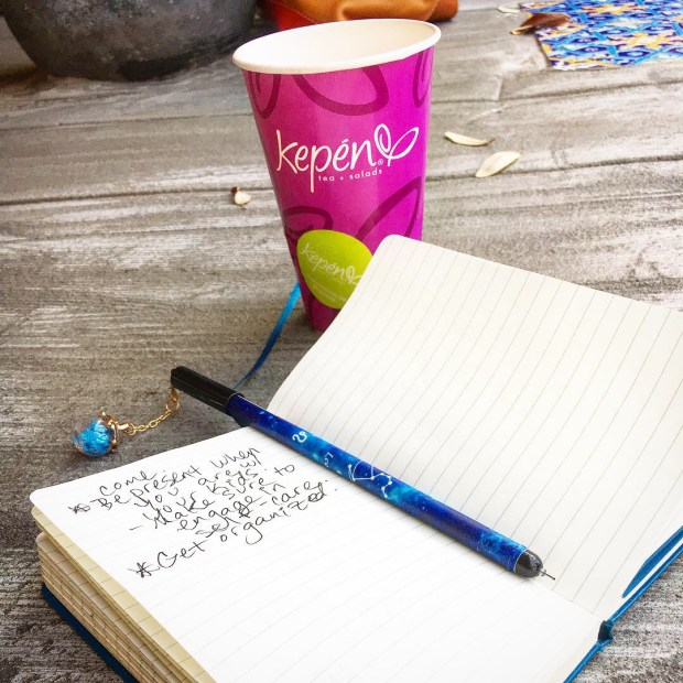 An open journal with a pen sitting on the spine with a pink paper cup labeled Kepen