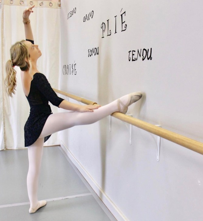 Stretching on the barre at my dance studio.