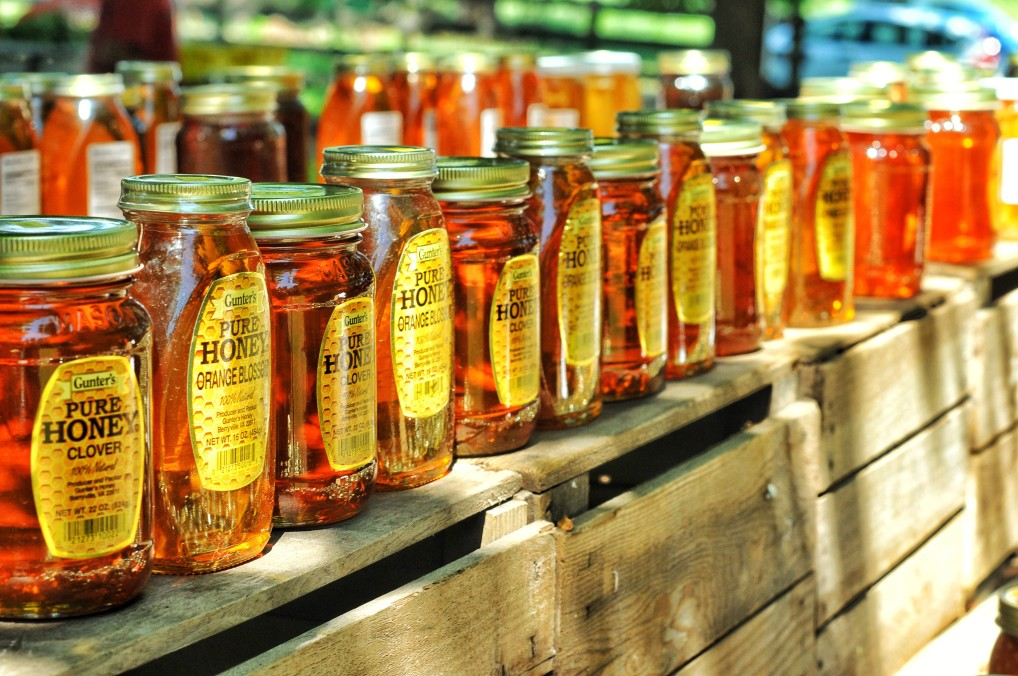 jars of honey on stand in a sunny day