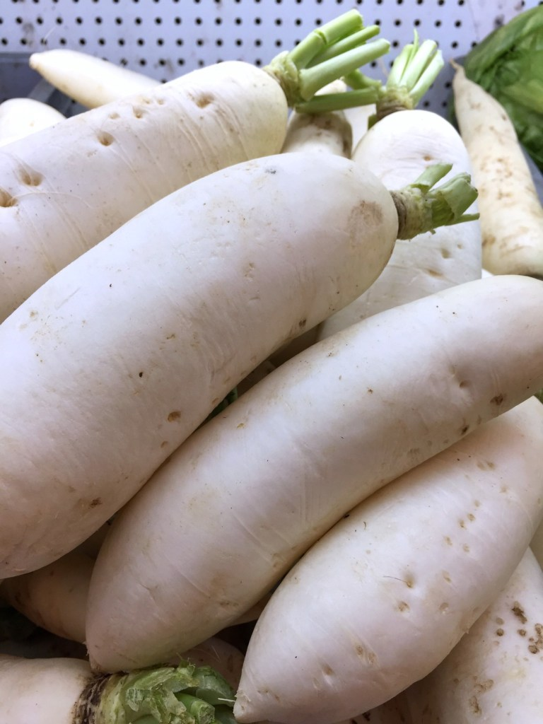 A close up of a pile of white daikon radishes