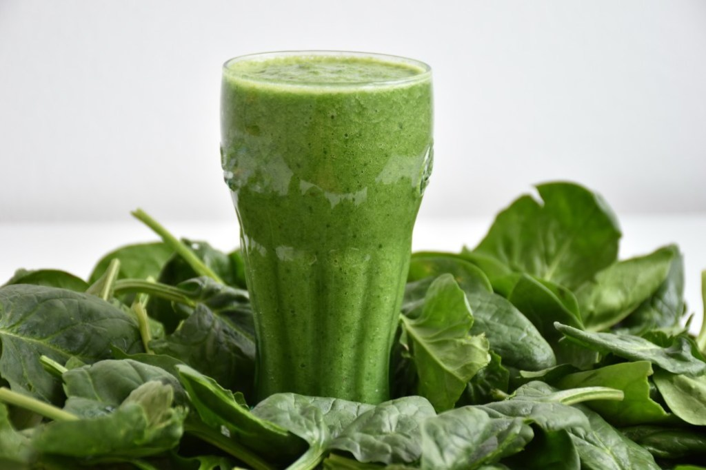 Smoothie Garden bunch of spinach surrounding a green smoothie