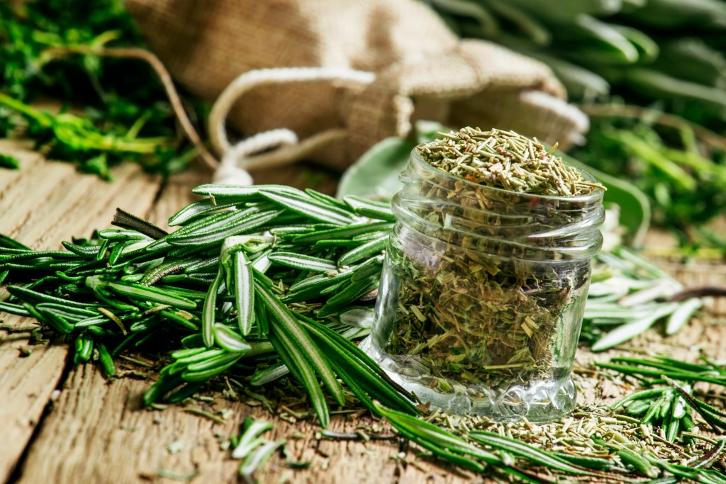 Dried rosemary in a glass jar, branches of fresh rosemary, vintage wooden background, selective focus