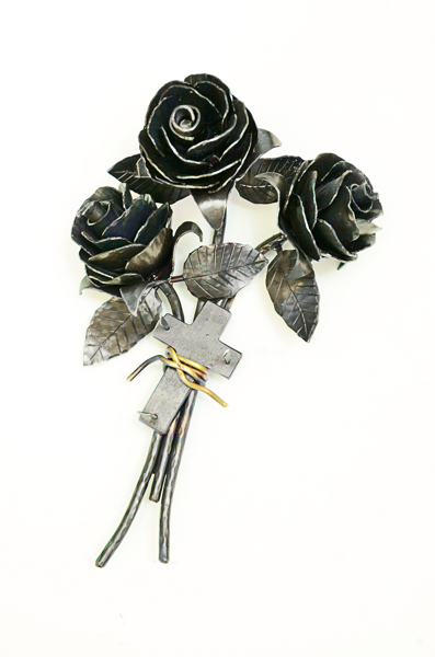 Picture of metalwork sculpture of three roses with leaves and thorns tied with a brass wire and a cross, made by Jim Davis.