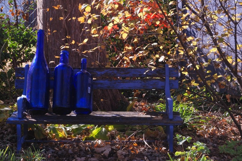 Three large cobalt blue bottles sit in a child's bench in a fall garden.