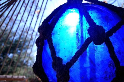 Light shining through a cobalt blue fishing float and you can see the cords of a hammock hanging near.