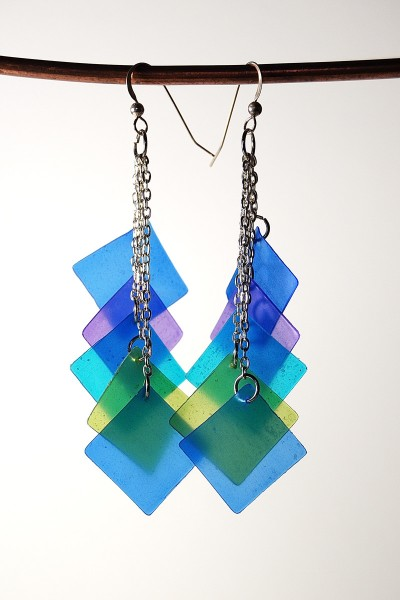 Artistic earrings made with dangling blue squares made from translucent polymer clay tinted with alcohol inks.