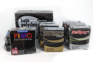 Various brands of black polymer clay packages.