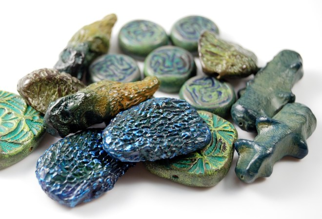 Polymer clay beads in green and blue tones, rustic and organic bead styles.