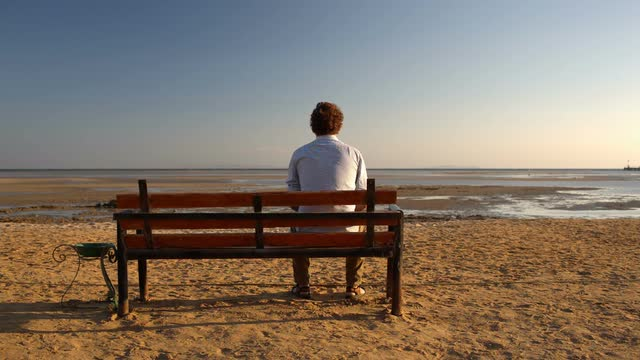 young-man-sitting-alone-on-the-bench-on-the-beach_7ko1ebtb__m0000