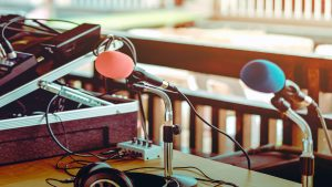 Jim & Ben Hughes, two microphones with red and blue spongesplaced on a stand with earphones on the table
