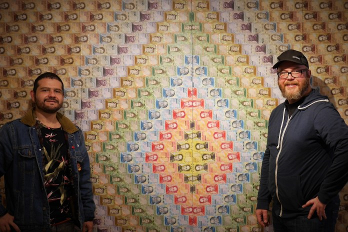 Andrés Chapparo, left, and Justin Rovig use defunct Venezuelan bolivar notes in their Bogotá art show this month. Photo: Steve Hide.
