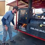 John stoking the fire at Owhyhee BBQ's trailer