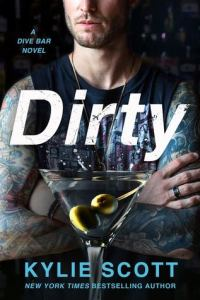 a tattooed male wearing a cut-off tee with a martini glass in front of him