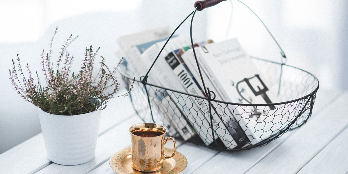Basket of books on a table next to a plant