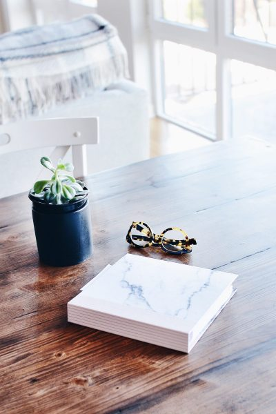 Table with a plant, book, and glasses