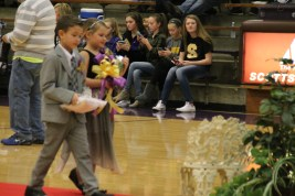 Photo by: Nicaila Mata --- Little Prince and Princess Casen Owens and Addison Elliott walk towards their seats for the ceremony. Owens carried the Queen's crown, while Addison carried her bouquet.