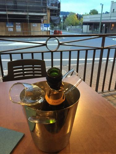 bottle of veuve clicquot in ice bucket on a table with street view of bowral