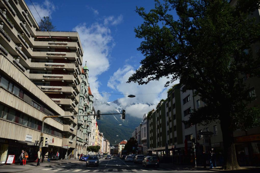 city street with buildings and mountains in the background innsbruck