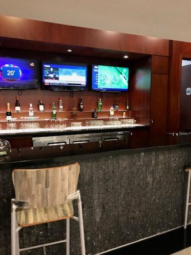 bar and seat and tvs at business class lounge medellin airport