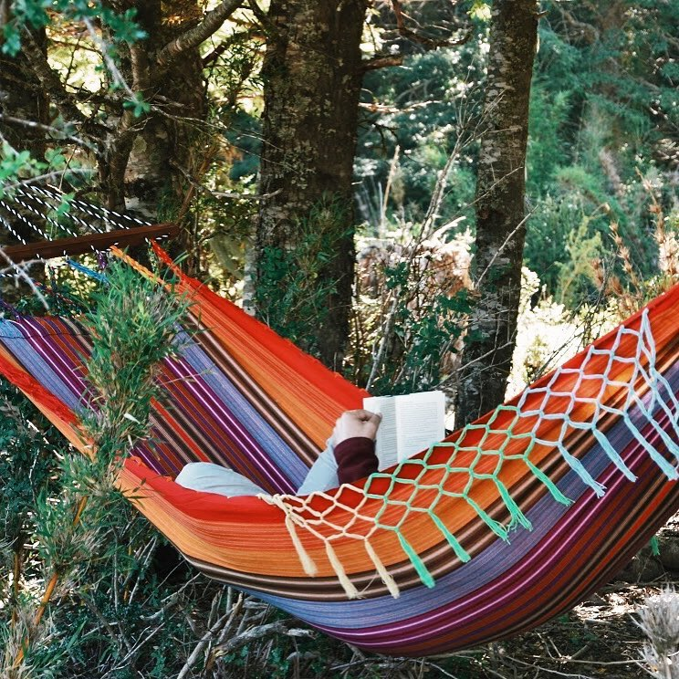 colourful hammock in the forest with a person inside