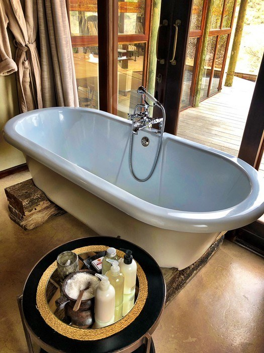 bathtub with glass wall behind and table with toiletries in front at kwandwe