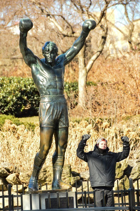 rocky statue in philadelphia with man posing in front