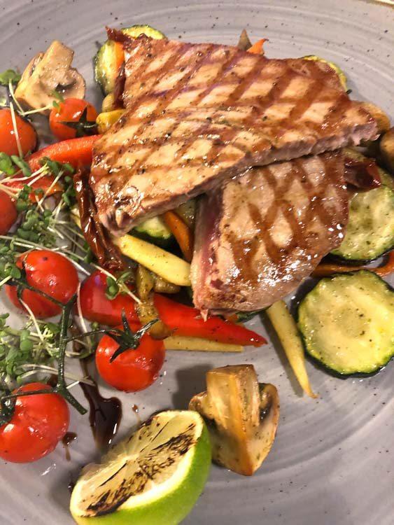 Tuna steak with vegetables on plate at hotel kurshi restaurant jurmala