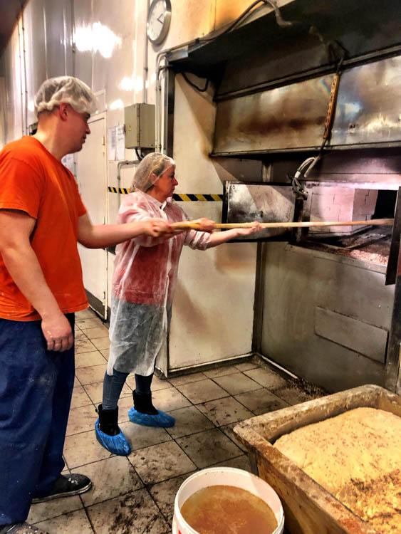 laci bakery oven with people putting in loaves