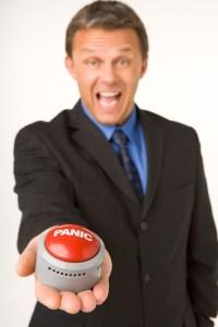 Businessman Holding A Panic Button