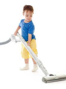 Toddler is cleaning room with vacuum cleaner isolated on white