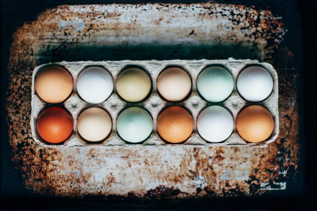 a photo of a carton of different colored eggs