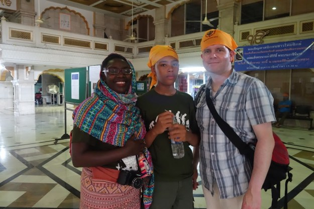 """Myself, """"The Music Producer"""", and """"The Tall Young Gentleman"""" donning bright yellow scarves and a colourful shawl at the Sikh temple in Bangkok, Thailand."""
