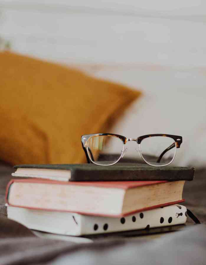 book; books; pile of books; reading books; glasses; spectacles; reading glasses; bed; bedside; reading in bed; bedroom; room; comfy bed; bed; pillow; cushion; furnishings; home; house; stay home; stay at home; keep your distance; don't travel; flatten the curve; social distancing; safer at home; shelter in place;