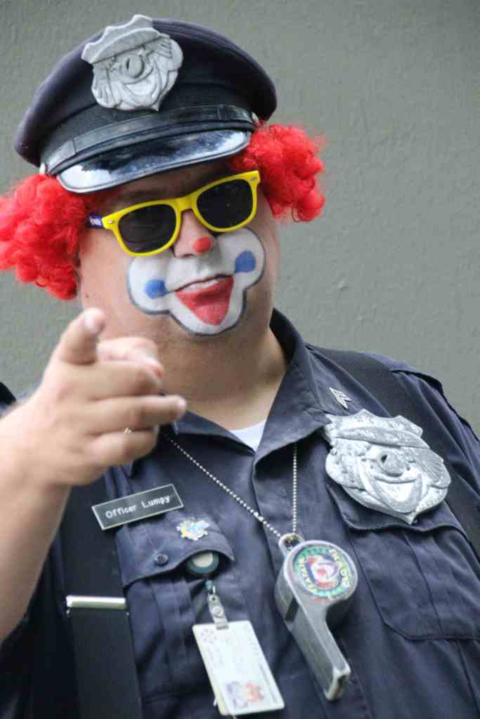 clown, police officer; policeman; police constable; officer; officer of the law; police officer clown; police officer with clown make up; police officer with make up; police officer pointing; pointing; funny; humour; humor; man; travel; USA; America; United States;
