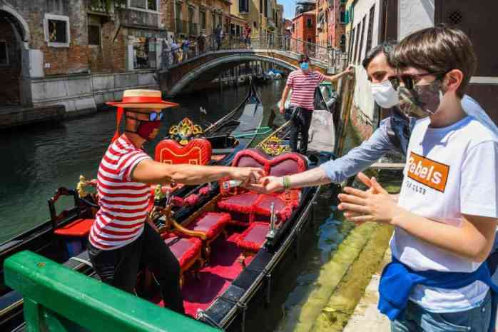 A gondolier (L) sprays sanitizer on his customers' hands prior to going for a gondola ride on a canal in Venice on June 12, 2020 as the country eases its lockdown aimed at curbing the spread of the COVID-19 infection, caused by the novel coronavirus. - Photo by ANDREA PATTARO/AFP via Getty Images