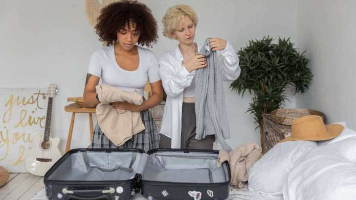 two girls are folding clothes to put in a luggage