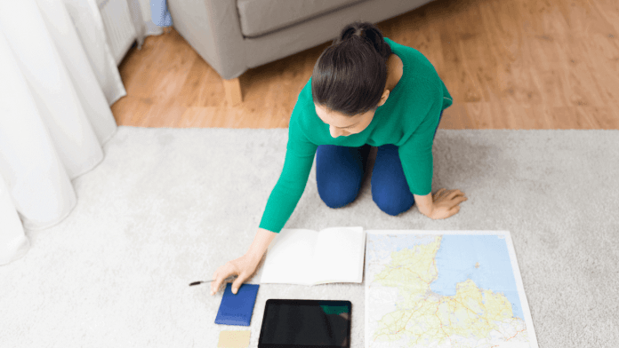 a woman holding a book and pen with an opening map