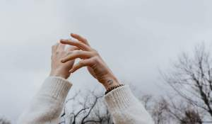 person wearing white sweater raising hands under white sky