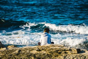 person sitting on shoreline