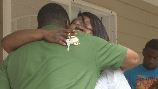 Warrick Dunn hugs a single-parent who is now a homeowner. (Photo Credit: Google Images)