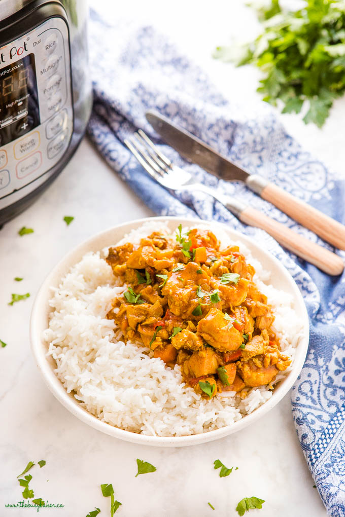 butter chicken made in the Instant Pot over rice in a white bowl